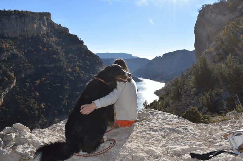 Chica con su perro con las vistas de fondo del congost
