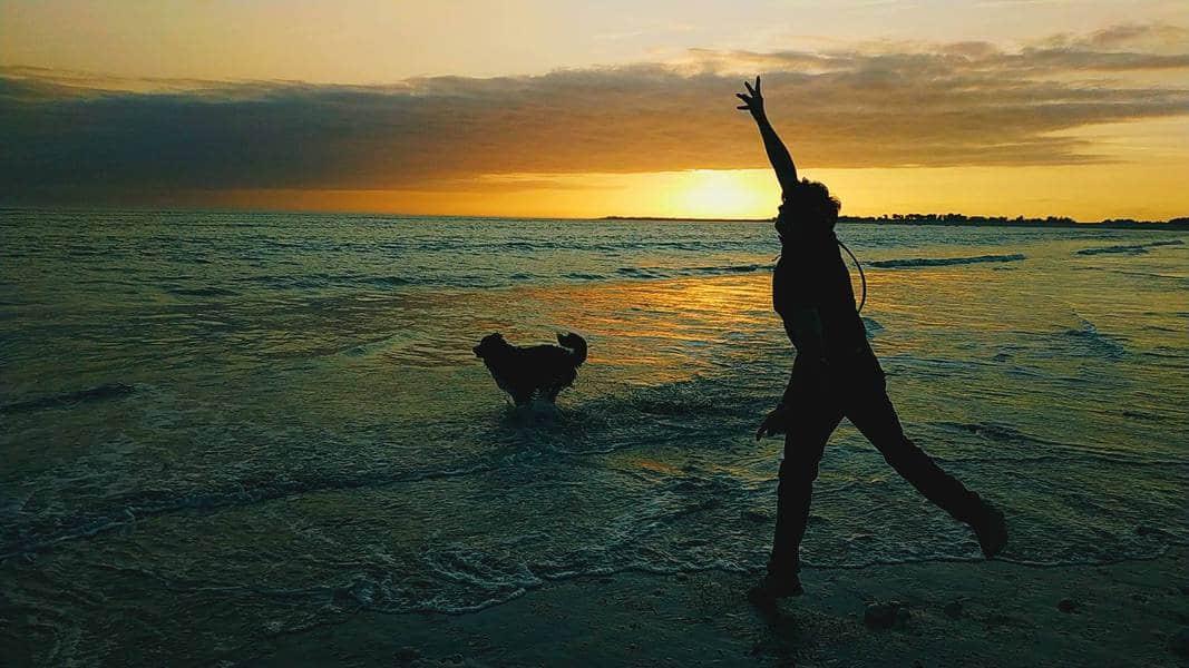 Foto contraluz hombre jugando con perro en playa